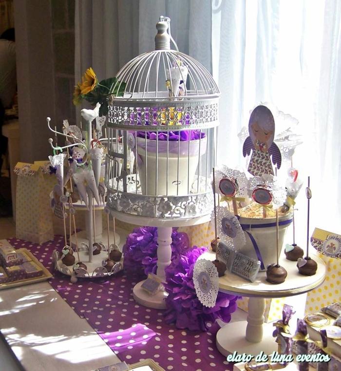 lila Deko Kommunion, ein lila Engel Stecker, ein weißer Käfig, lila Tischläufer