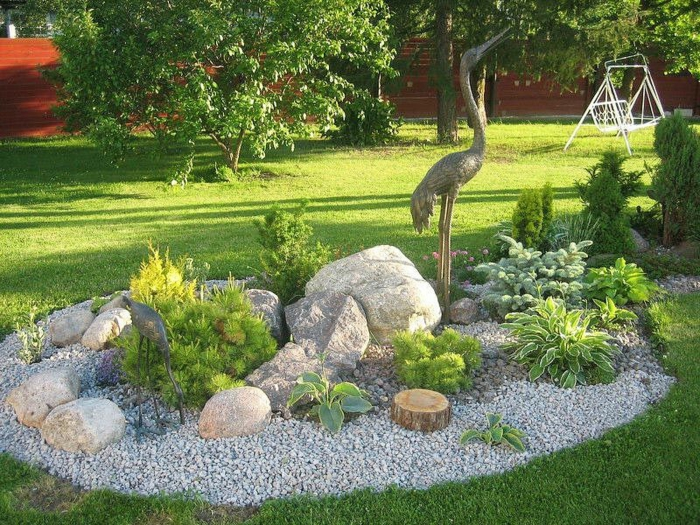 ein Kreis von Kies, eine Vogelfigur, große Steine, ein Rasen, Garten gestalten mit wenig Geld