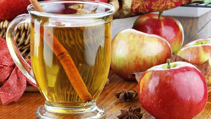 ein glas mit einem gelben apfelsaft und mit zimt, ein tisch aus holz und mit einem korb aus rattan und mit roten äpfeln und einer roten schleife, fruchtfliegenfalle essig