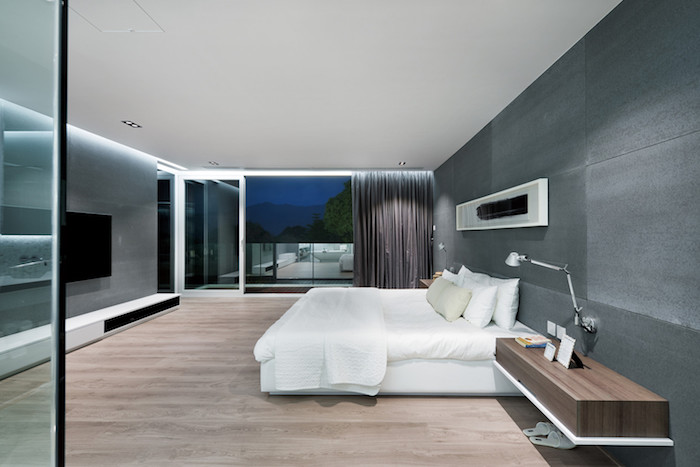 ein boden aus holz, ein großes schlafzimmer mit einem weißen bett mit weißen kleinen und großen kissen und ein großer schwarzer fernseher, ein kleiner brauner tisch aus holz und eine kleine graue lampe