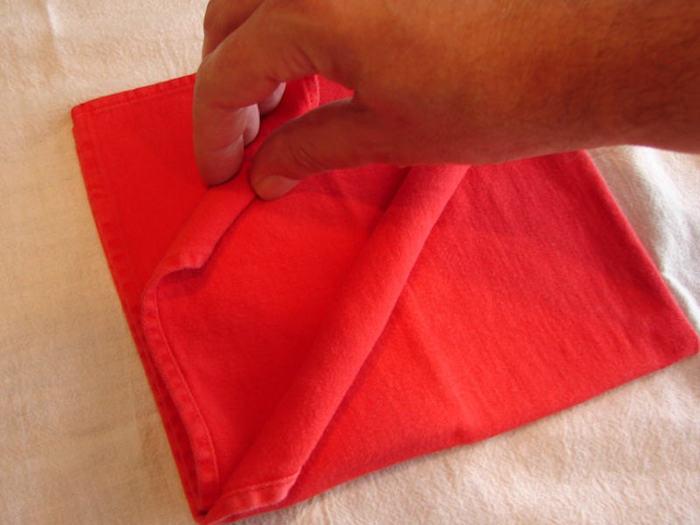 eine weiße decke und eine kleine rote gefaltete serviette und eine hand, servietten falten einfach und wirkungsvoll