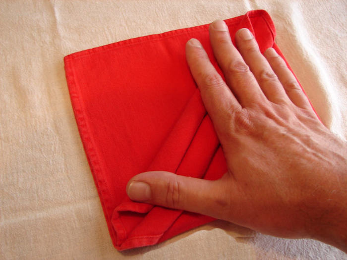 eine weiße decke und eine kleine rote gefaltete serviette und eine hand, servietten falten anleitung, eine bestecktasche falten