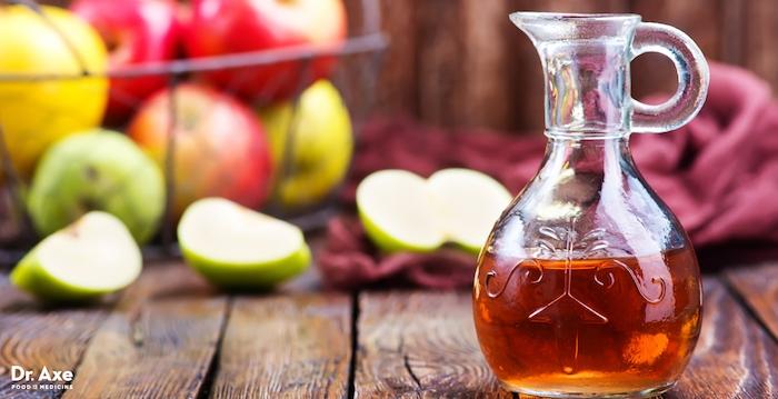 eine kanne aus glas und mit einem orangen apfelessig, ein tisch aus holz und mit vielen grünen, roten und gelben äpfeln, fruchtfliegenfallen selber machen