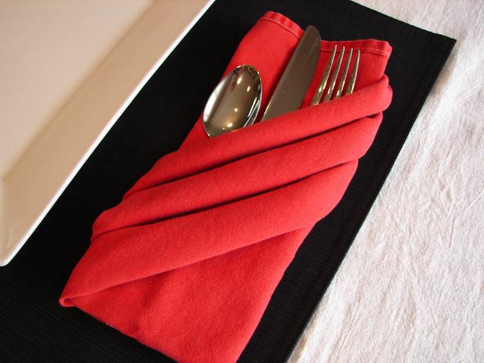 servietten falten hochzeit, ein tisch aus holz und eine rote gefaltete bestecktasche mit einem messer, einem löffel und einer gabel, bestecktaschen falten