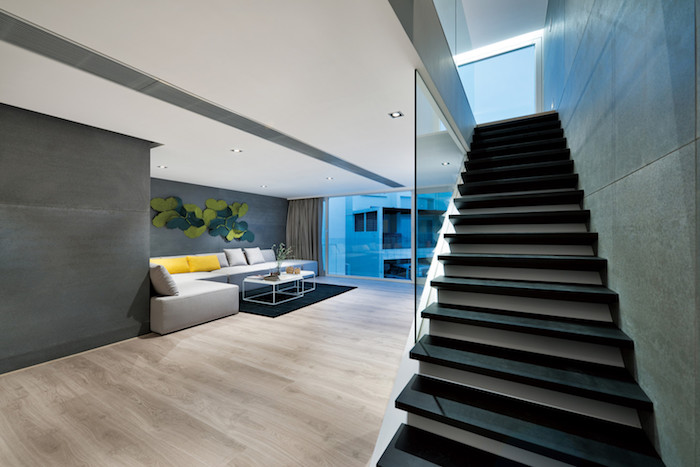 eine schwarze treppe und ein boden aus holz, ein wohnzimmer einrichten, ein weißes sofa mit grauen und gelben kissen und ein weißer tisch und ein schwarzer teppich