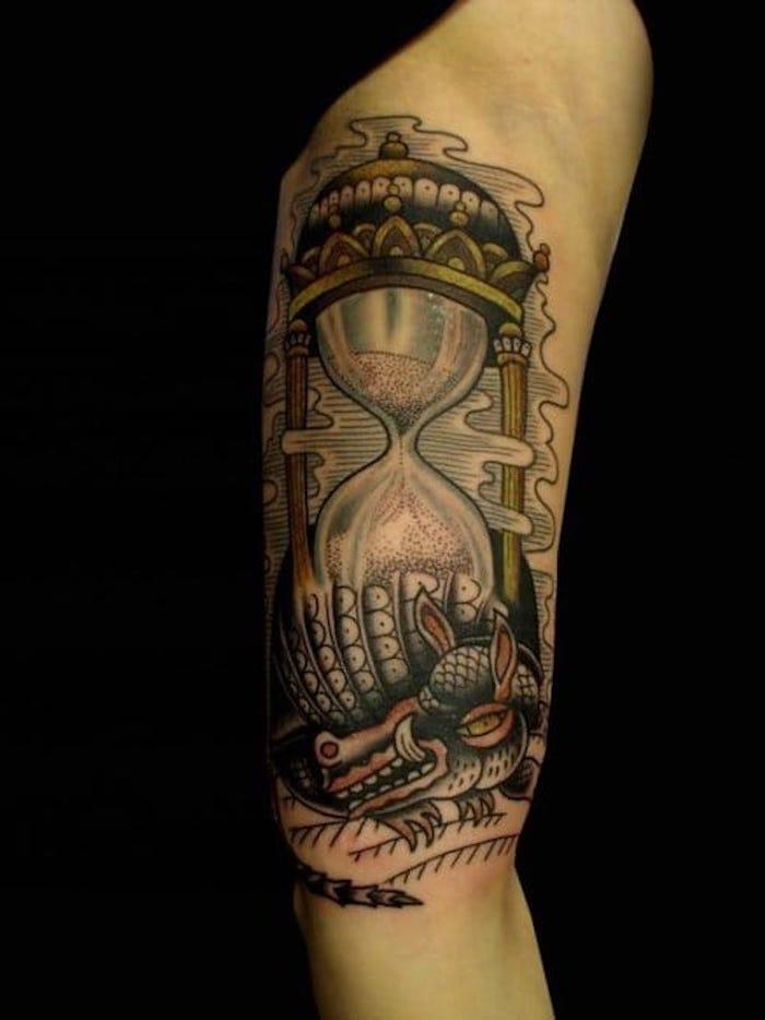 ei kleiner grüner drache mit kleinen gelben augen und mit scharfen zähnen, eie hand mit einem tattoo mit einer großen sanduhr mit einem violetten sand, tattoo sanduhr bedeutung