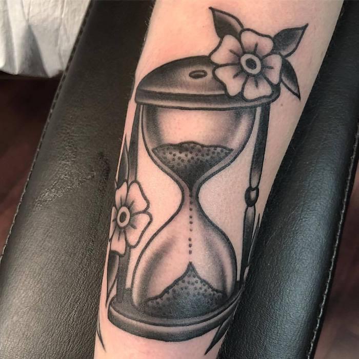 eine großé schwarze tätowierung mit zwei kleinen weißen blumen mit kleinen schwarzen blättern, eune hand mit einem tattoo mitr einer schwarzen großen sanduhr mit einem schwarzen sand, sanduhr tattoo bedeutung
