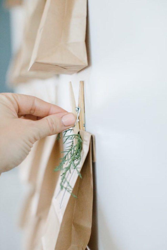 eine weiße wand mit einem Wäscheklammer und kleiner grünen blättern und mit kleinen braunen papiertüten und eine hand, eine diy bastelanleitung schritt für schritt