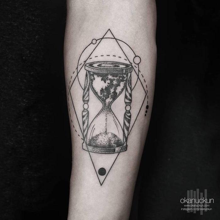 eine hand mit einer großen schwarzen tätowierung, sanduhr tattoo bedeutung, ein tattoo mit einer großen schwarzen sanduhr mit weltkarte und mit einem schwarzen sand
