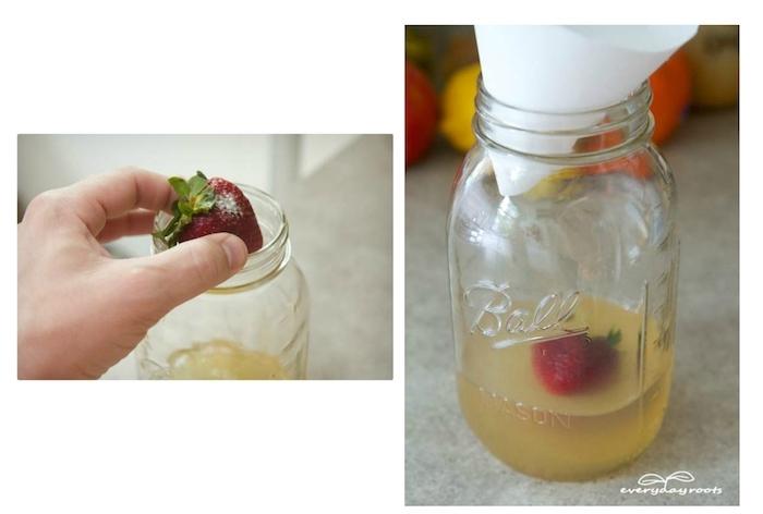 ein glas mit einem gelben apfelessig, eine fruchtfliegenfalle selber baue, ein großer glas mit einem weißen großen trichter und mit roten erdbeeren mit grünen blättern