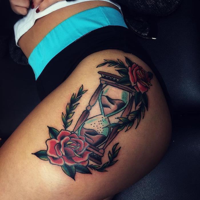 junge frau mit bein mit einem großen farbigen sanduhr tattoo, eine braune sanduhr aus holz und mit einem braunen sand, tattoo mit zwei großen roten rosen mit vielen grünen blättern, sanduhr symbol