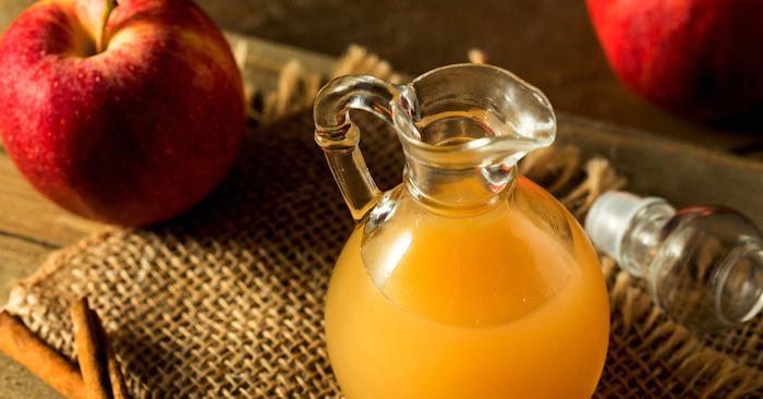 ein tisch aus holz und eine große kanne mit einem orangen apfelsaft, beste fruchtfliegenfalle, ein tisch mi zwei roten äpfeln und mit zimt