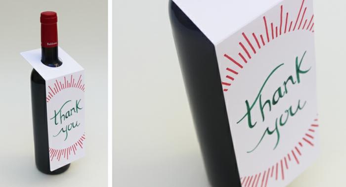 eine Weinflasche verpacken, um danke schön zu sagen, eine weiße Karte mit roter Verzierung