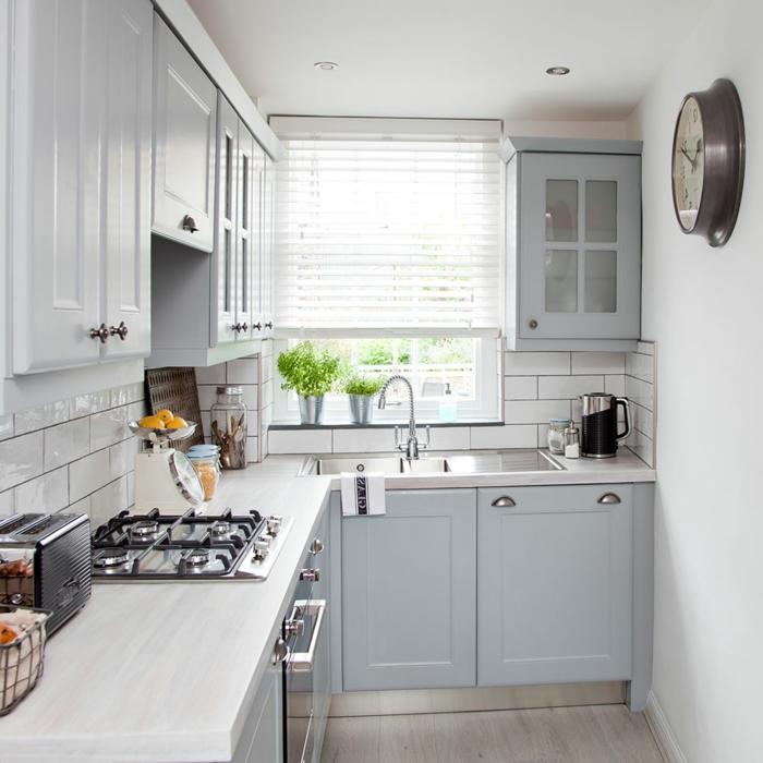eine kompakte Küche, hellgraue Wand, eine vintage Wanduhr, ein Laminatboden
