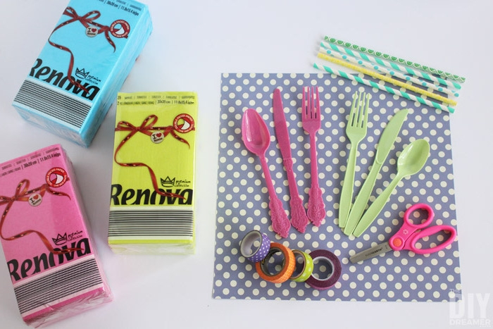 gelbe, pinke und blaue servietten, eine kleine pinke schere, strohhalme und violette und grüne messer, löffel und gabeln