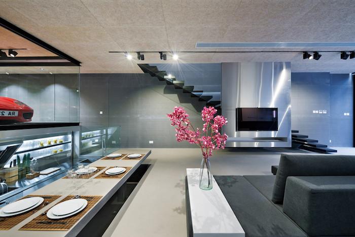 ein kleiner weißer tisch mit einer vase mit pinken blumen, ein wohnzimmer einrichten, ein wohnzimmer mit einem großen schwarzen fernseher und einer schwarzen treppe, ein tisch mit weißen tellern und ein roter wage, ein graues sofa mit grauen kissen