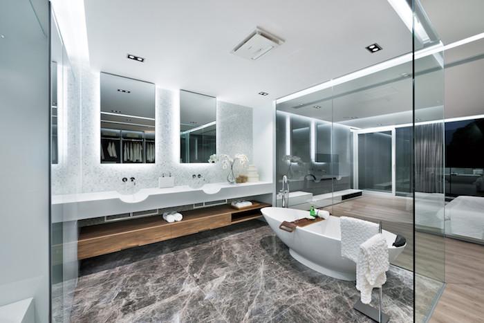 eine kleine weiße badewanne und ein badezimmer mit weißen wänden und braunen fliesen, zwei großen spiegeln und einem großen weißen waschbecken und kleinen weißen blumen, zimmer einrichten ideen