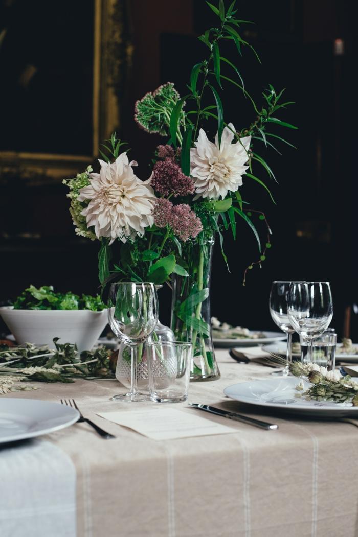 hohe Vase mit weißen und lila Blumen, grüne Zweige auf dem Tisch, Deko Kommunion