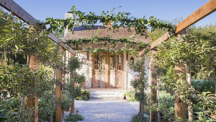 ein gemütliches Landhaus mit Bogen und Kletterpflanzen, Gartenweg aus Steinen, Garten gestalten mit wenig Geld