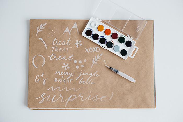eine große braune papiertüte mit kleinen schneeflocken , weißen blättern und bergen mit schnee und bunten farben, papiertüten basteln ohne kleben