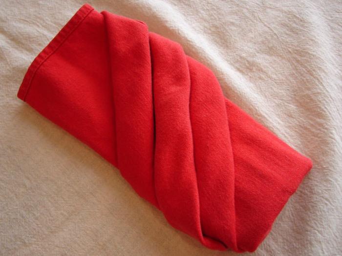 eine weiße decke und eine rote gefaltete bestecktasche, servietten falten hochzeit, tischdeko ideen
