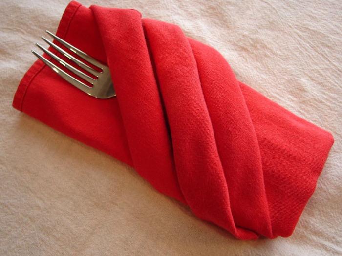 tischdeko selber machen, eine weiße decke und eine grpße rote bestecktasche mit einer gabel, eine rote bestecktasche falten