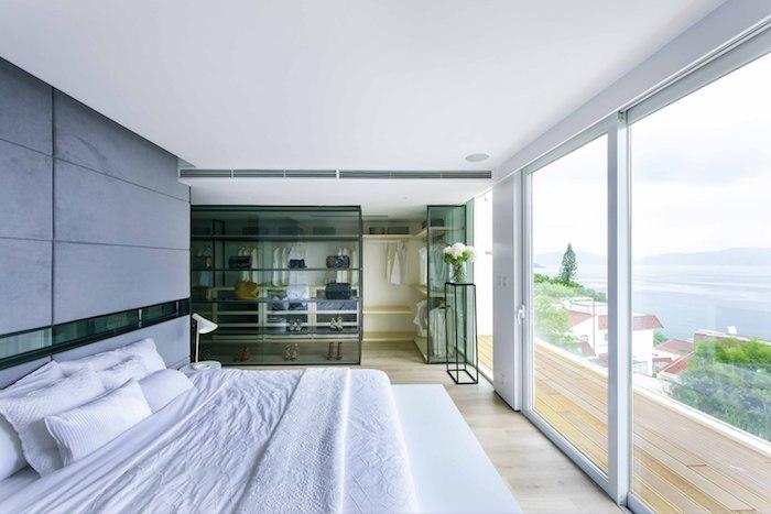 zimmer einrichten ideen, ein kleines schlafzimmer mit einem weißen bett mit kleinen und großen kissen und mit einem großen fenster, meer und bäume mit grünen blättern