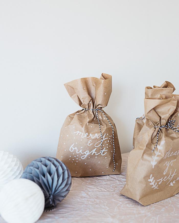 eine weiße decke und eine weiße wand und zwei kleine selbst gemachte braune papiertüten mit weißen blättern, ästen und schneeflocken
