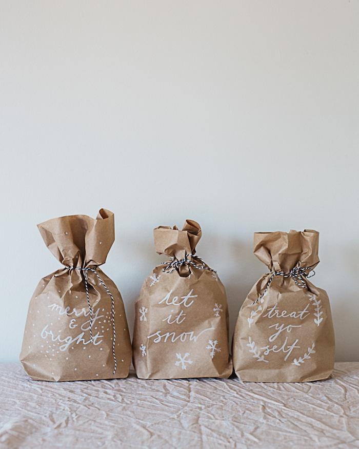 drei kleine braune gefaltete papiertüten mit kleinen weißen schneeflocken und ästen mit weißen blättern, eine weiße decke und eine weiße wand
