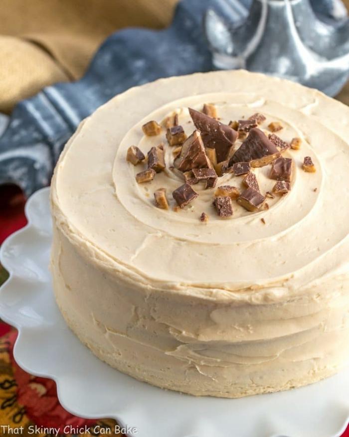 eine cremige Torte, kleine Stücke Pralinen darauf, schnelle Geburtstagstorte, eine weiße Decke