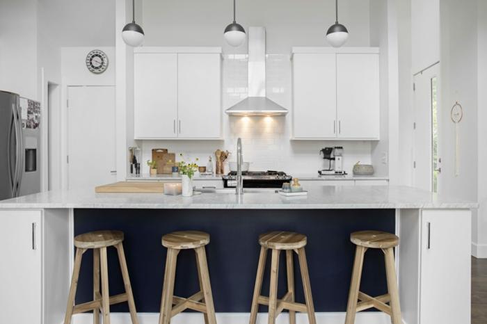 weiße Regale, blaue Theke. Wand Deko, vier Hocker aus Holz, hängende Lampen