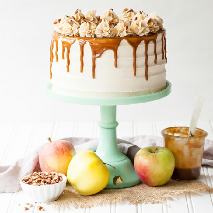 grüner Tortenständer, eine weiße Torte mit Karamell Glasur, Toffiffe Krümmel als Dekoration