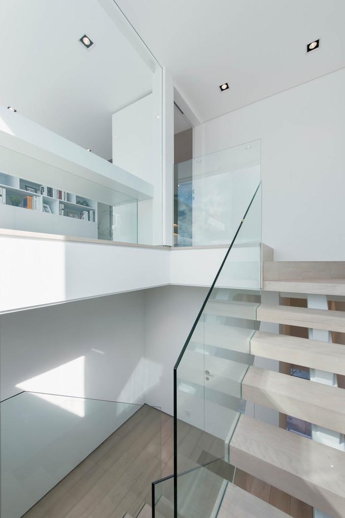 eine treppe und viele kleine weiße und orange bücher, ein zimmer mit großen weißen wänden und kleinen schwarzen lampen und mit einem boden aus holz