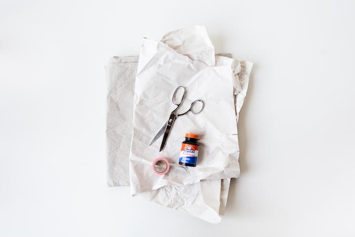 eine schere und kleber und ein blatt papier und ein weißer tisch, eine bastelanleitung, papiertüten selber machen