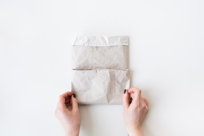 zwei hände mit einem schwarzen nagellack und mit einer gefalteten papiertüte aus einem alten weißen papier und ein weißer tisch, papiertüten basteln