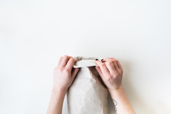 eine hand mit einem tattoo am handgelenk, hände mit einem schwarzen nagellack und eine gefaltete weiße tüte aus einem alten papier, eine diy anleitung, papiertüten falten