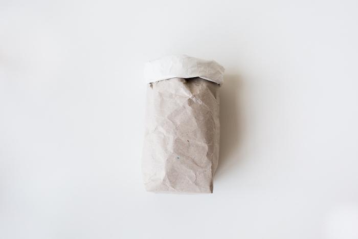 ein weißer tisch und eine kleine gefaltete weiße tüte aus einem alten weißen papier, eine diy bastelanleitung, papiertüten basteln ohne kleben