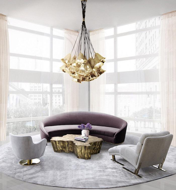 Wandfarbe Weiß, lila Sofa und graue Sessel, verspielter kronleuchter, Vase mit lila Blumen