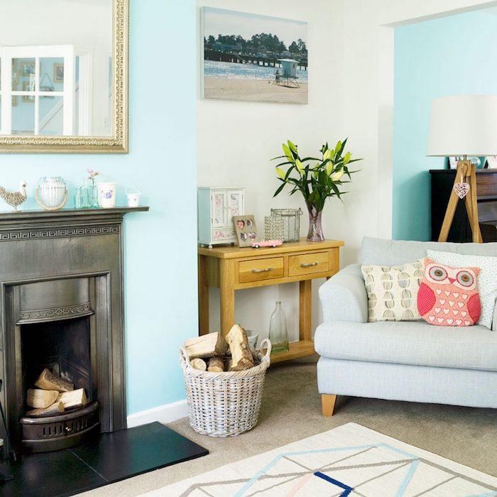 Wohnzimmer in Hellblau, großer Spiegel über dem Kamin, hellblauer Sessel, Kissen in Form von Uhu