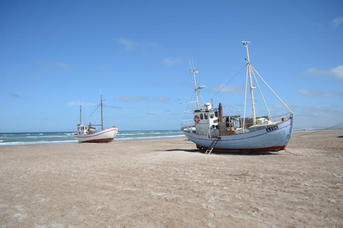 Boote am Strand, blauer Himmel und weißer Sand an der dänischen Nordseeküste