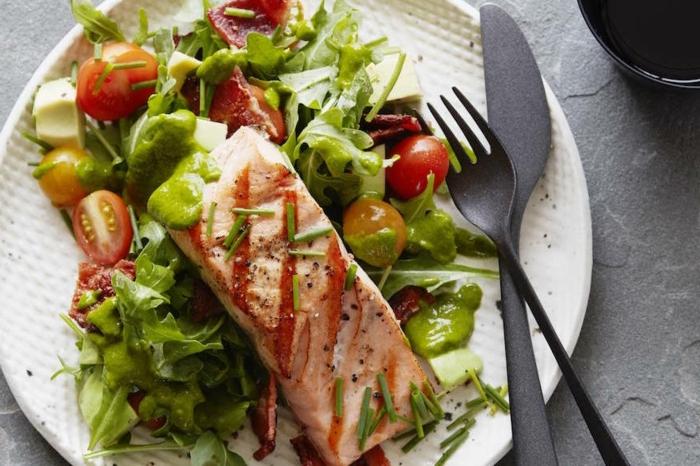 ein Stück gegrillter Fisch, Rucola, Kischtomaten, ausgefallene Salate für Grillparty
