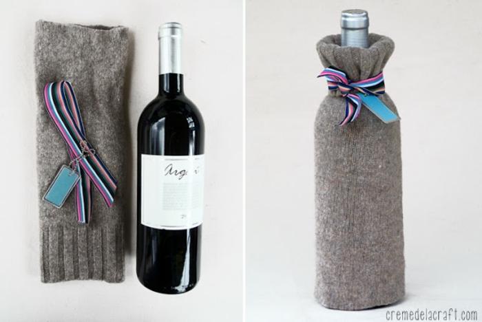 mit einem Ärmel von grauen Pullover und mit einer bunten Schleife Flaschen verpacken