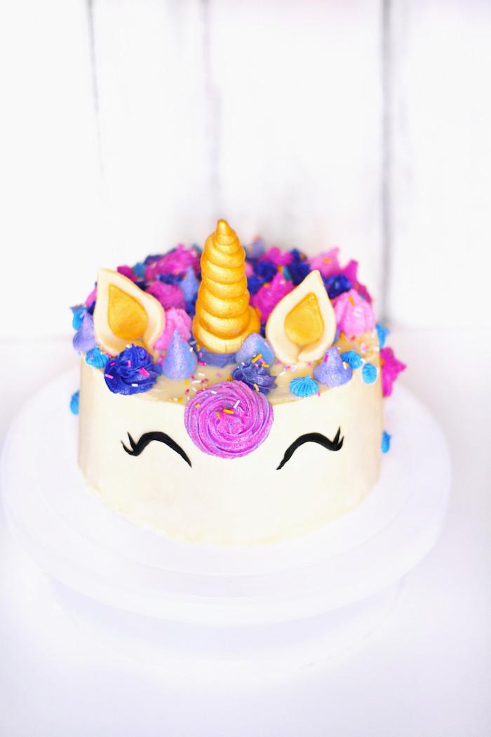 Einhorn Torte mit Fondant, goldenes Horn, blaue und lila Blüten, schöne Idee für Kindergeburtstag