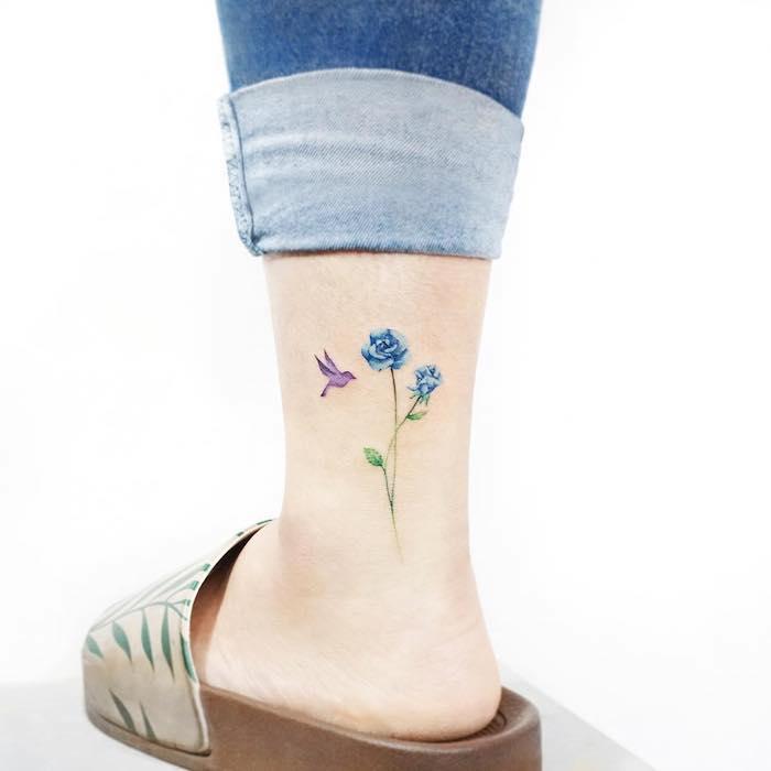 Tattoo an der Wade für Frauen, blaue Blume und lila Vogel, zartes Tattoo Motiv