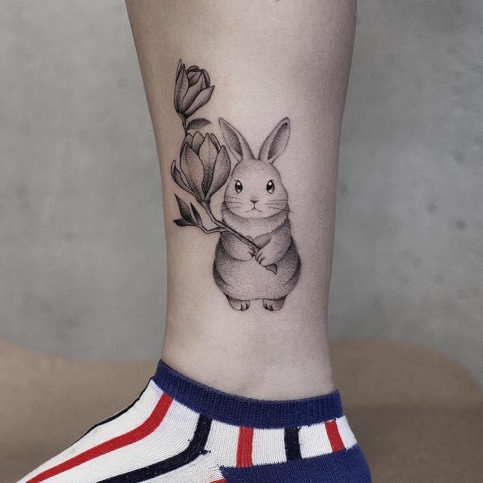 Zartes Tattoo Motiv, Kaninchen mit Blume, Tattoo Ideen für Frauen
