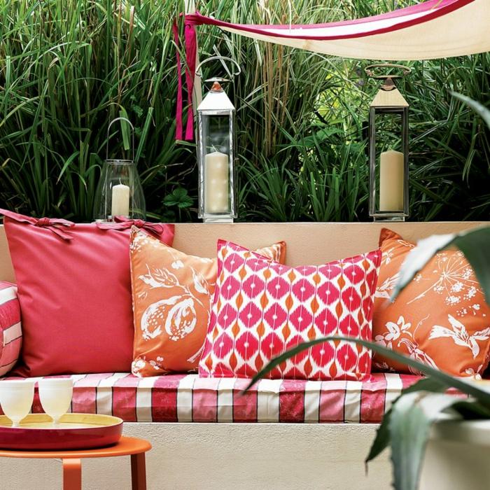 ein hoher Gras, bunte Kissen auf Gartensofa, Kerzenständer, Garten anlegen günstig