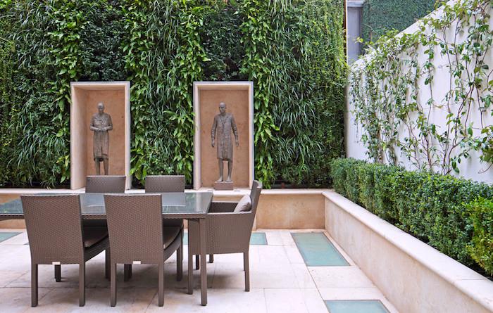 gartenbeet gestalten, zwei statuen, gartendeko, wand mit grünen pflanzen, mooswand