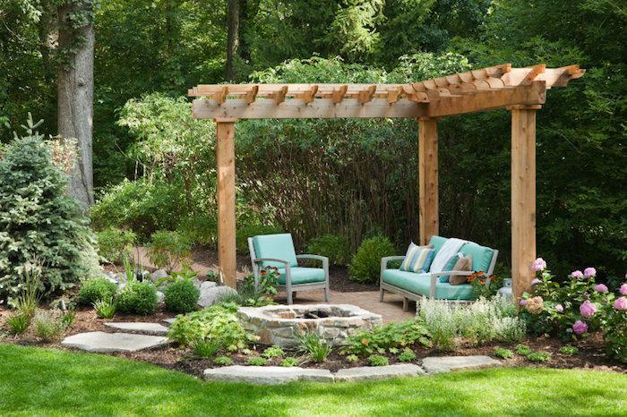 gartenecke gestalten, polstermöbel, gartenmöbel mit blauen sitzkissen, natur, bäume