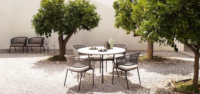 gartenecke gestalten, naturstein, weiße wand, kleine bäume, strühle aus raten und aluminium