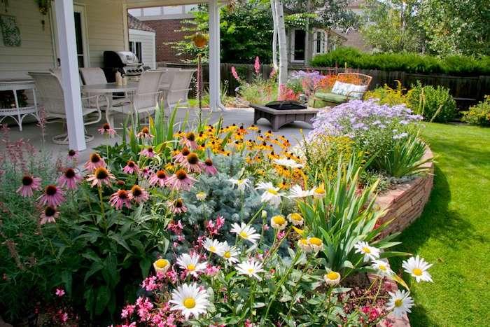 gartenecke gestalten, haus mit varanda, viele bunte blumen, sitzecke, vorgarten